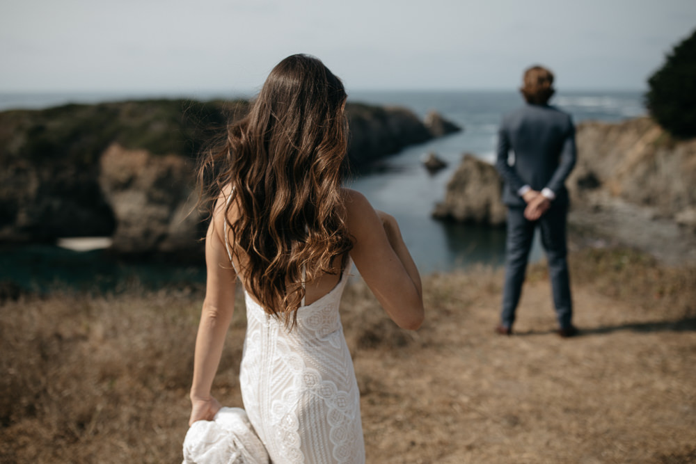 Bride and groom first look on the coastline of California